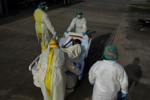 Healthcare workers transfer a COVID-19 patient at United Memorial Medical Center in Houston, Texas on July 2, 2020; some hospital intensive-care units there are on the verge of being overwhelmed by the pandemic