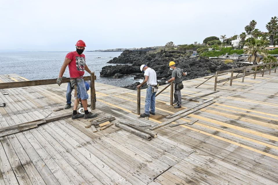 Workers during the restoration of a bathing establishment after the safety measures against Covid-19 to be followed for 'phase 2' have been established in order to ensure the resumption of activities, after the lockdown, and ensuring the protection of the health of workers and users on May 13, 2020 in Catania, Italy. Italy was the first country to impose a nationwide lockdown to stem the transmission of the Coronavirus (Covid-19), and its restaurants, theaters and many other businesses remain closed. (Photo by Fabrizio Villa/Getty Images)