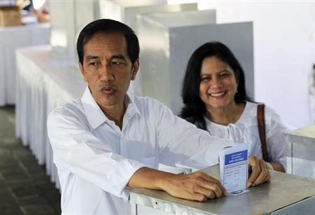 Jakarta governor and presidential candidate from PDI-P party, Widodo, and his wife Iriana cast their ballot papers during voting in parliamentary elections in Jakarta