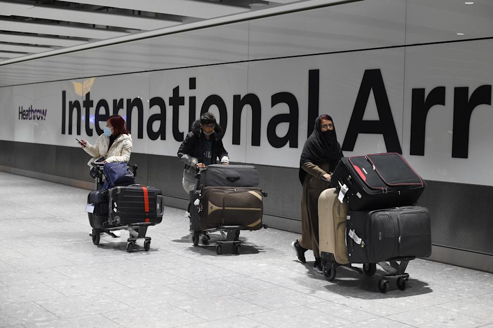 Passengers push luggage through the Arrival Hall of Terminal 5 at London's Heathrow Airport after arriving into the UK following the suspension of the travel corridors. Passengers arriving from anywhere outside the UK, Ireland, the Channel Islands or the Isle of Man must have proof of a negative coronavirus test and self-isolate for 10 days. Picture date: Monday January 18, 2021.