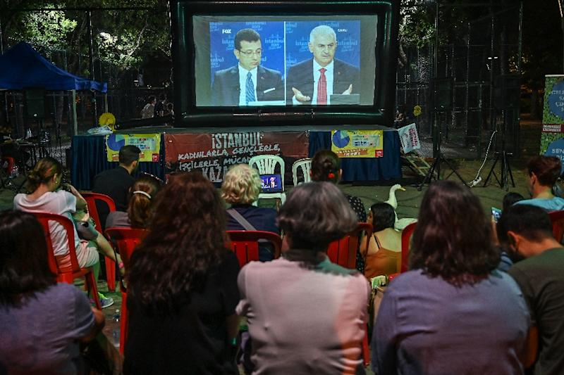 People watch a live broadcast of a televised debate between Istanbul's mayoral candidates Binali Yildirim (R) of Turkey's ruling Justice and Development Party (AKP), and Ekrem Imamoglu (L) of the main opposityion Republican Peoples Party (CHP). The re-run election is next Sunday