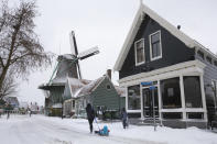 A woman pulls her child on a sled in Zaandam, near Amsterdam, Netherlands, Sunday, Feb. 7, 2021. Snow and strong winds pounded The Netherlands, with more cold and snow expected in the days ahead. (AP Photo/Peter Dejong)