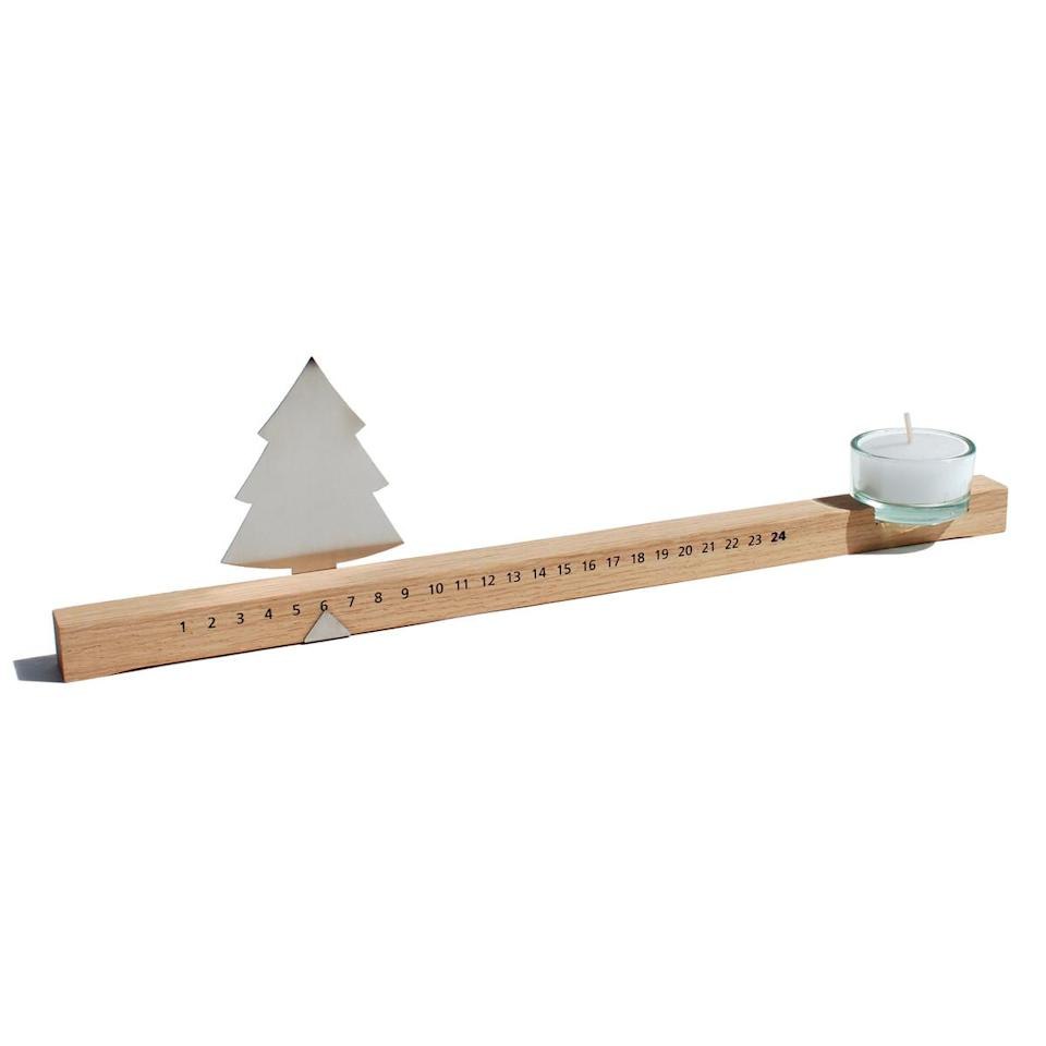 """<p>Crafted from oak, stainless steel and glass, this minimalist countdown to Christmas is definitely heirloom material. The closer the tree moves to the candle, the sooner the holidays are approaching.</p><p>£24.90 <a href=""""https://www.connox.co.uk/categories/seasonal/advent-calendar/adventsleiste-design-im-dorf.html"""" rel=""""nofollow noopener"""" target=""""_blank"""" data-ylk=""""slk:Connox"""" class=""""link rapid-noclick-resp"""">Connox</a></p>"""