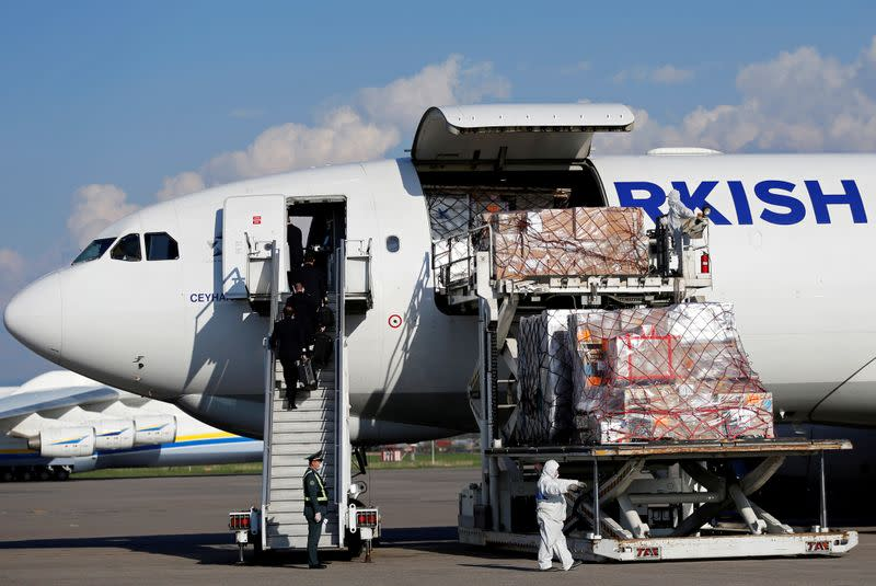 Workers unload a shipment of medical supplies from Turkey intended to combat the spread of the coronavirus disease (COVID-19), at Almaty International Airport
