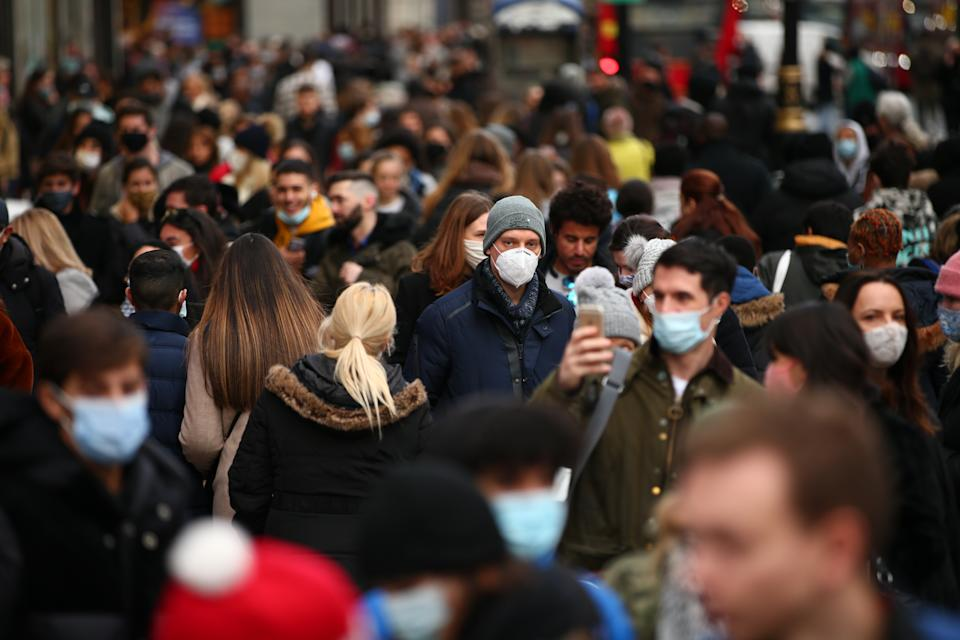 Shoppers, some wearing face masks, walk along a busy Oxford Street in London. (Getty)