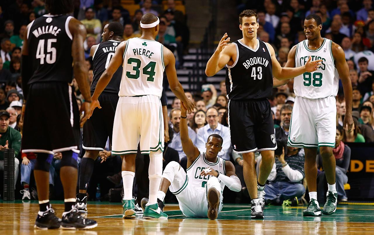 BOSTON, MA - NOVEMBER 28: Rajon Rondo #9 of the Boston Celtics is helped up by teammate Paul Pierce #34 after being fouled in front of Kris Humphries #43 of the Brooklyn Nets during the game on November 28, 2012 at TD Garden in Boston, Massachusetts. NOTE TO USER: User expressly acknowledges and agrees that, by downloading and or using this photograph, User is consenting to the terms and conditions of the Getty Images License Agreement.  (Photo by Jared Wickerham/Getty Images)