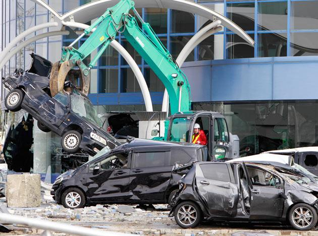 A wrecked car is pulled from a building following the March 11 earthquake triggered tsunami at the port in Sendai, Japan, Thursday, March 17, 2011. (AP Photo/Mark Baker)