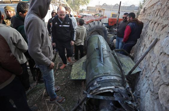 Civilians gather next to a fragment of a ground-to-ground missile fired by Syrian regime forces (AFP via Getty Images)