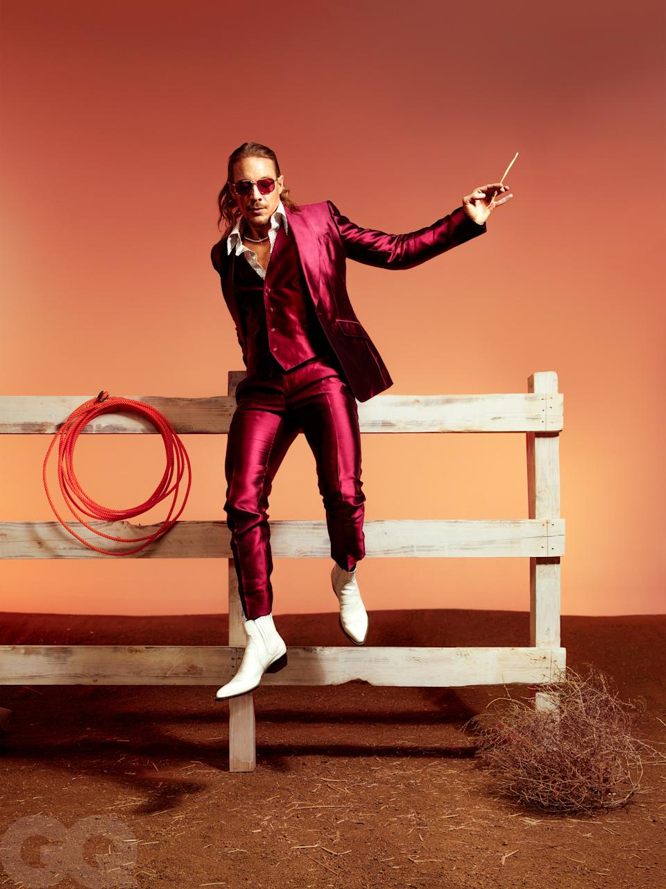 """<cite class=""""credit"""">Suit, $4,395, and shirt, $1,195, by Dolce & Gabbana / Boots, $378, by Matt Shultz x Frye / Sunglasses, $310, by Persol / Necklace, $67,200, by Shay</cite>"""