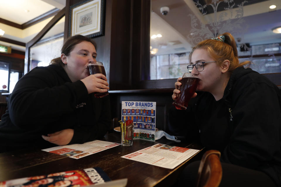 Libby Jones, right, with her colleague Shannon Maiden, both nurses from Great Ormond Street hospital who have just finished an overnight shift, have a pint of cider at the Shakespeare's Head pub, which will be reopening for the first time to serve indoor customers since the end of the latest coronavirus lockdown, in London, Monday, May 17, 2021. (AP Photo/Alastair Grant)
