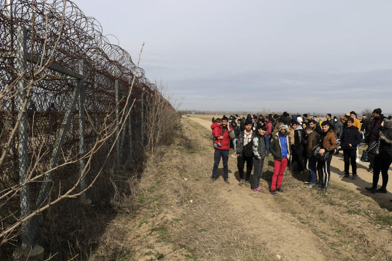 Greek border guards patrol, left, as migrants wait at he Turkey-Greece border, in Pazarkule, Edirne, Turkey, Friday, Feb. 28, 2020. NATO envoys were holding emergency talks Friday at the request of Turkey following the killing of 33 Turkish soldiers in northeast Syria, as scores of migrants gathered at Turkey's border with Greece seeking entry into Europe. (IHA via AP)