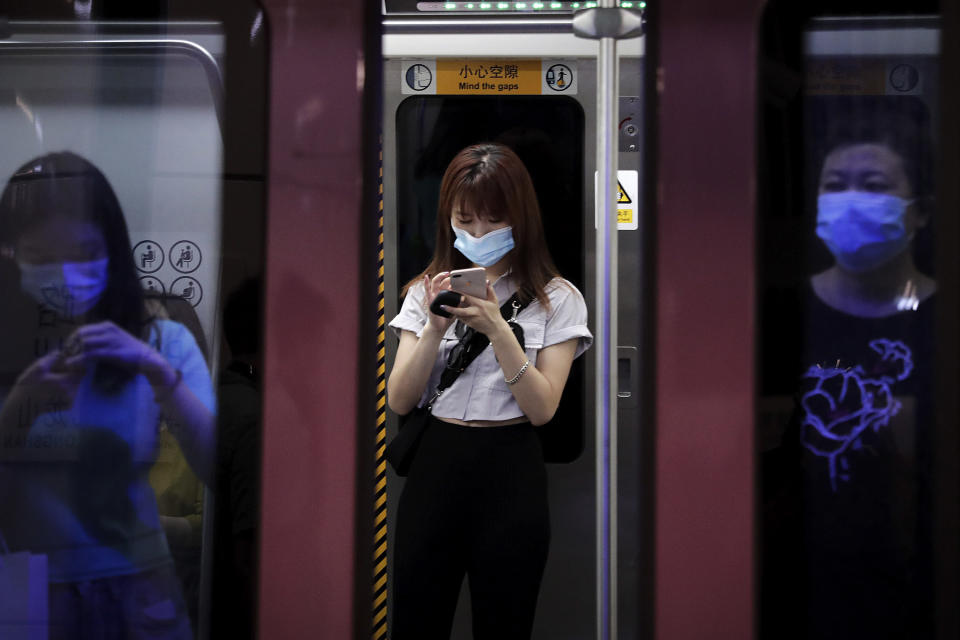Commuters wearing face masks to protect against the new coronavirus ride in a subway train in Beijing, Wednesday, July 29, 2020. China reported more than 100 new cases of COVID-19 on Wednesday as the country continues to battle an outbreak in Xinjiang. (AP Photo/Andy Wong)