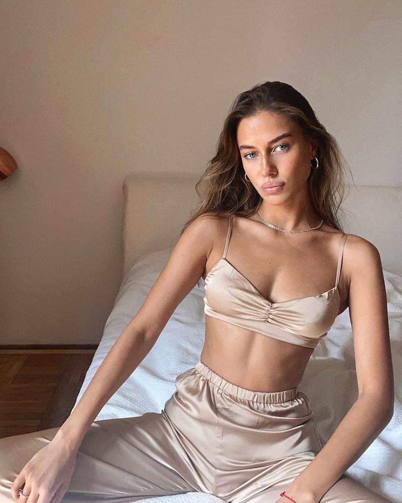 Nicole Poturalski wearing a beige bra top and pants while sitting on a bed