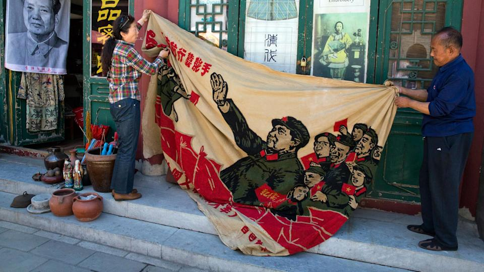 "Vendors unfurl a banner from 1969 depicting former Chinese leader Mao Zedong as he ""inspects the great army of the Cultural Revolution""."