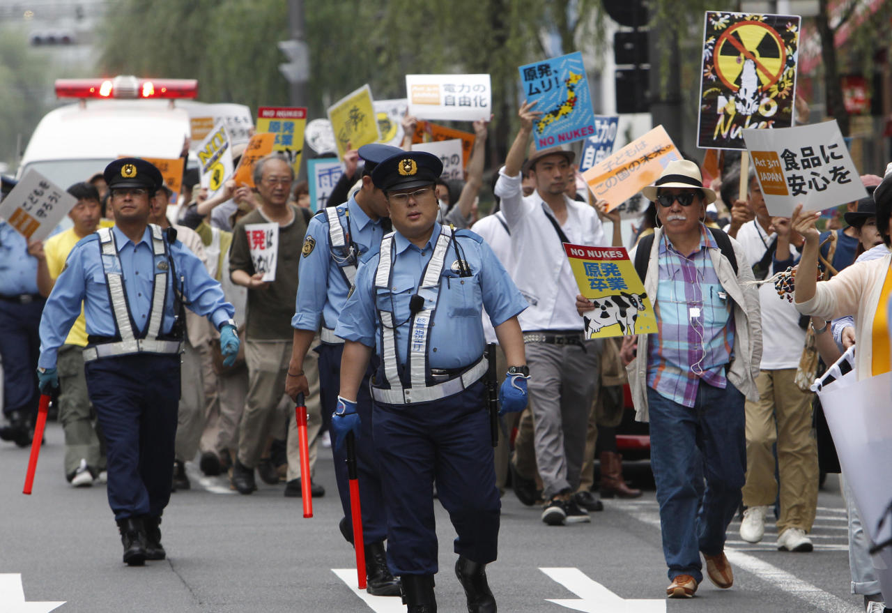 Police officers watch traffic as demonstrators walk past the headquarters of Tokyo Electric Power Co. (TEPCO) during their anti-nuclear power protest in Tokyo Sunday, June 26, 2011. (AP Photo/Shizuo Kambayashi)
