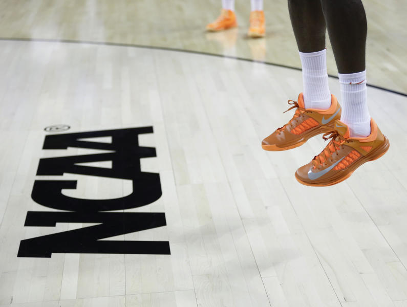 FILE - In this March 21, 2013, file photo, an athlete jumps near the NCAA logo during practice for a second-round game of the NCAA college basketball tournament in Austin, Texas. Defying the NCAA, California's governor signed a first-in-the-nation law Monday, Sept. 30, that will let college athletes hire agents and make money from endorsements — a move that could upend amateur sports in the U.S. and trigger a legal challenge. (AP Photo/Eric Gay, File)