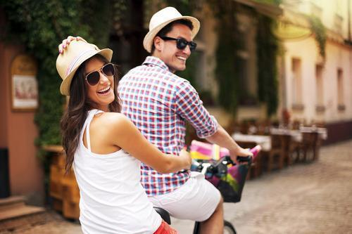couple riding a bicycle in city
