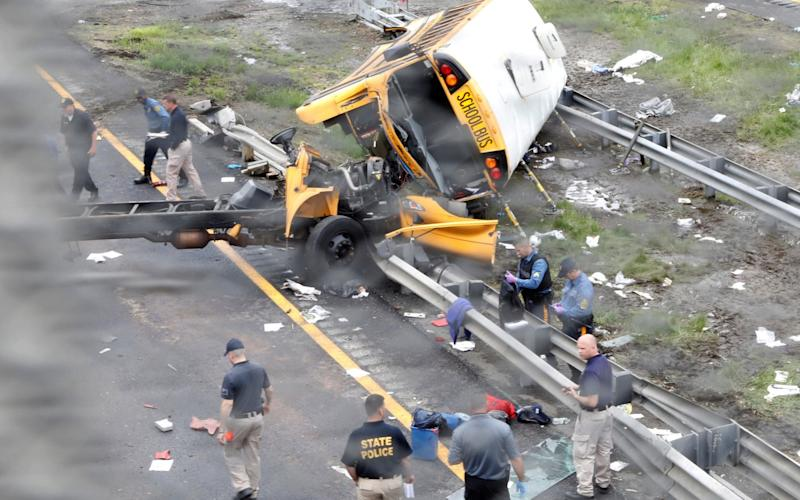 Police stand near the wreckage of a school bus on Interstate 80 following an accident with a dump truck in Mount Olive Township - REUTERS