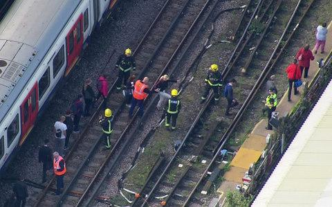 mergency workers help people to disembark a train near the Parsons Green - Credit: AP