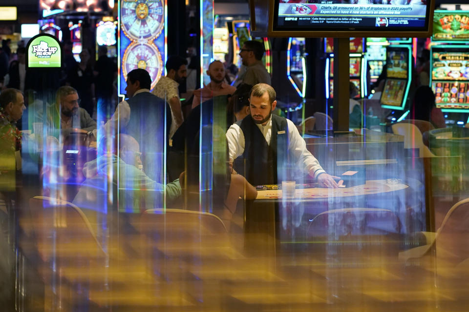 In this June 24, 2021, photo, a dealer distributes cards to gamblers during the opening night of Resorts World Las Vegas in Las Vegas. Las Vegas fully reopened and lifted restrictions on most businesses June 1, though many casino-resorts had already returned to 100% capacity before that with approval from state regulators. Visitor numbers, while not at their pre-pandemic highs, have grown by double digits four months in a row. But this progress is threatened as Nevada this week saw the highest rate of new COVID-19 cases in the country. (AP Photo/John Locher)