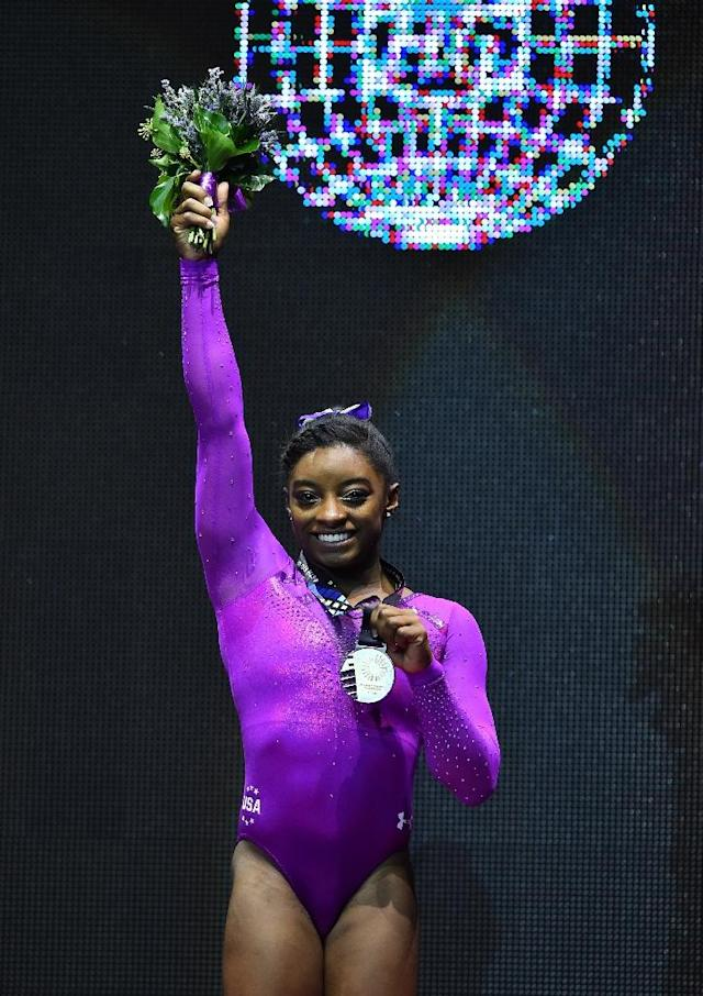 American Simone Biles poses with her gold medal after the women's balance beam final at the 2015 World Gymnastics Championship in Glasgow, Scotland, on November 1, 2015 (AFP Photo/Ben Stansall)