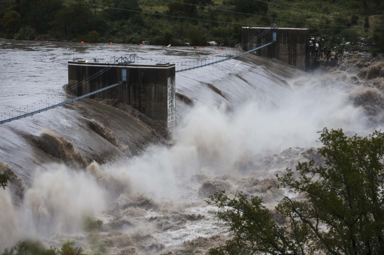 """Water from the Colorado River pours over the Max Starcke Dam, Tuesday Oct. 16, 2018, in Marble Falls, Texas. The Llano and Colorado rivers meet at Kingsland and the National Weather Service said both were experiencing """"major flooding."""" A flash flood warning was in effect. (Amanda Voisard/Austin American-Statesman via AP)"""