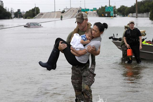 <p>AUG. 27, 2017 – Houston Police SWAT officer Daryl Hudeck carries Catherine Pham and her 13-month-old son Aiden after rescuing them from their home surrounded by floodwaters from Tropical Storm Harvey in Houston. (Photo:David J. Phillip/AP) </p>