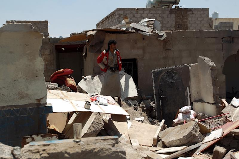 A Yemeni man looks at the ruins of his house, which was destroyed by Saudi-led coalition air strikes, near Sanaa Airport on March 31, 2015 (AFP Photo/Mohammed Huwais)