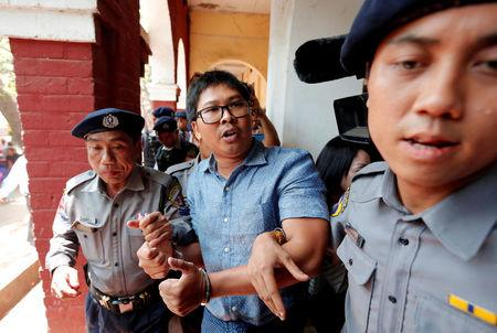 Detained Reuters journalist Wa Lone is escorted by police after a court hearing in Yangon, Myanmar March 28, 2018. REUTERS/Stringer
