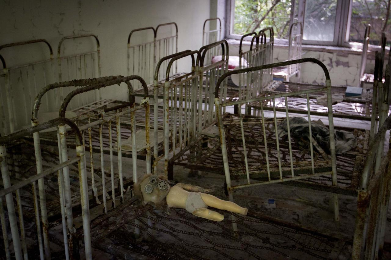 In this June 8, 2011 photo, a doll with a gas mask lies on the frame of a bed in the sleeping room of a kindergarten in the deserted town of in Pripyat, Ukraine, some 3 kilometers (1.86 miles) from the Chernobyl nuclear plant. Chernobyl and Fukushima are some 5,000 miles apart but have much in common. The towns nearest to each of these stricken nuclear power stations, in Ukraine and Japan, whose disasters struck 25 years apart, already reveal eerie similarities. (AP Photo/Sergey Ponomarev) ONE OF PAIR NO. 8