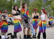 Football supporters are seen with LGBT pride flags outside of the stadium before the Euro 2020 soccer championship group F match between Germany and Hungary at the Allianz Arena in Munich, Germany,Wednesday, June 23, 2021. (AP Photo/Matthias Schrader)