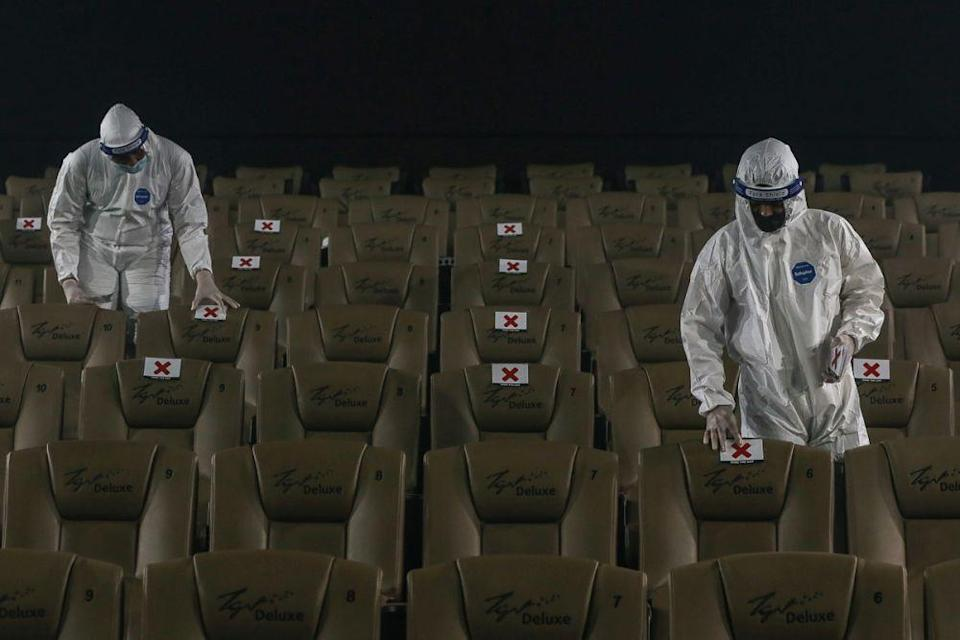 Workers in protective suits mark seats for social distancing at a movie theatre ahead of its reopening at TGV Cinemas in Central I-City, Shah Alam September 14, 2021. — Yusof Mat Isa
