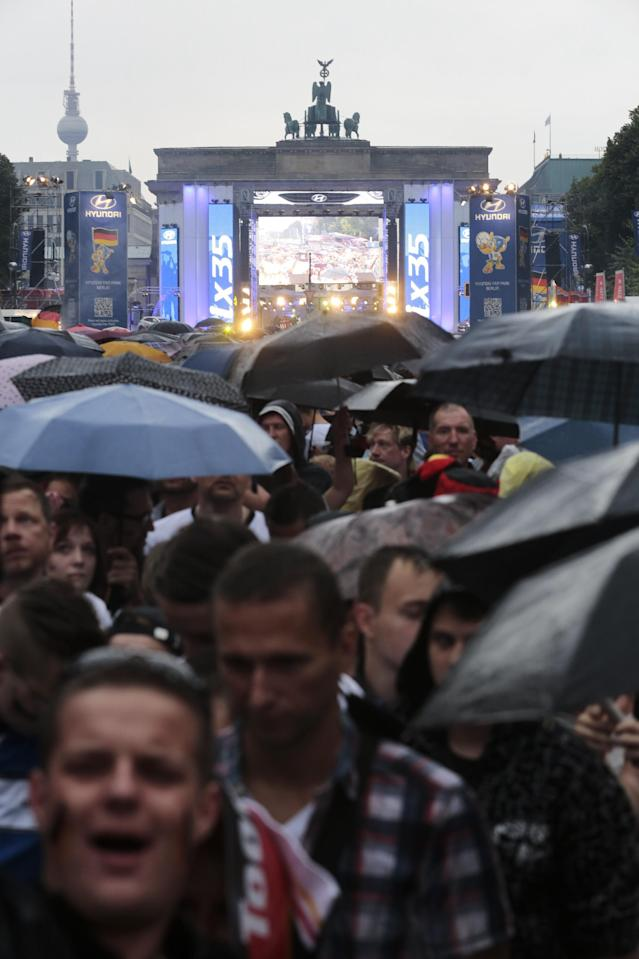 During heavy rain, thousands of German soccer fans wait for the live broadcast of the final match between Germany and Argentina at the soccer World Cup in Rio de Janeiro, Brazil, at a public viewing area called 'Fan Mile' in front of the Brandenburg Gate in Berlin, Sunday, July 13, 2014. (AP Photo/Markus Schreiber)