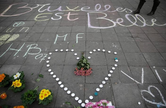 "A message written on the ground reads ""Brussels is beautiful"" next to flowers and candles at a makeshift memorial following attacks in Brussels (AFP Photo/Kenzo Tribouillard)"
