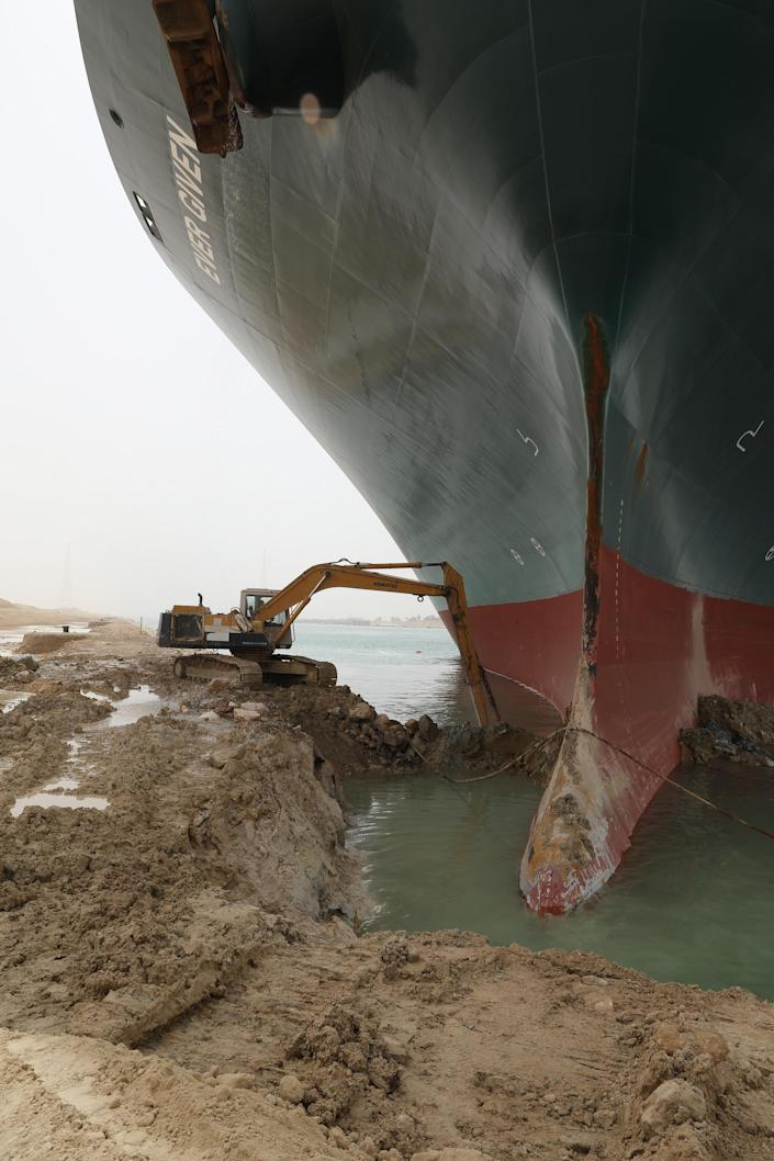An excavator works to remove sand from the bank of the Suez Canal amid efforts to dislodge the MV Ever Given container ship. / Credit: Suez Canal Authority