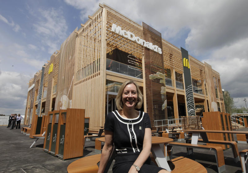 Jill McDonald, CEO of McDonald's UK, backdropped by the newly constructed McDonald's restaurant at the Olympic Park, poses for the photographers in east London, Monday, June 25, 2012. The restaurant is designed to be reusable and recyclable after the London 2012 Olympic and Paralympic Games. (AP Photo/Lefteris Pitarakis)