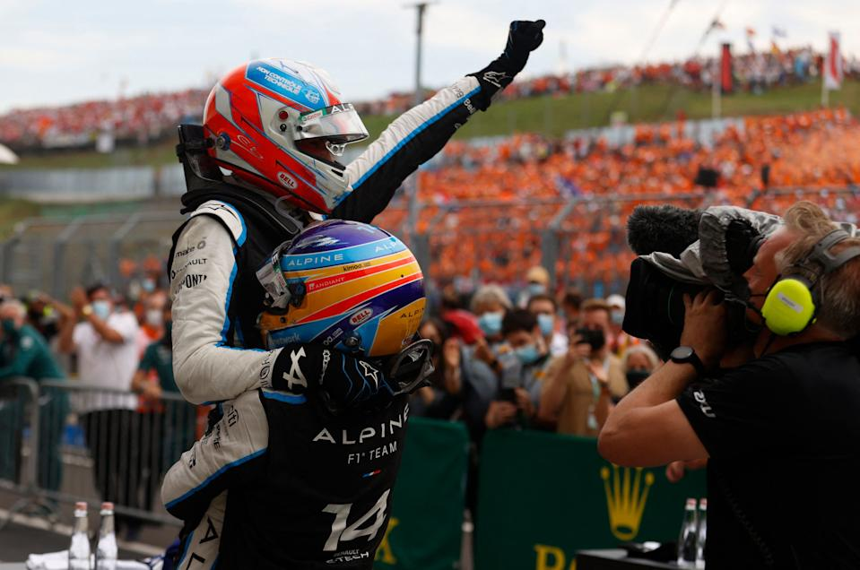 Alpine's French driver Esteban Ocon is carried by Alpine's Spanish driver Fernando Alonso after the Formula One Hungarian Grand Prix at the Hungaroring race track in Mogyorod near Budapest on August 1, 2021. (Photo by FLORION GOGA / AFP) (Photo by FLORION GOGA/AFP via Getty Images)