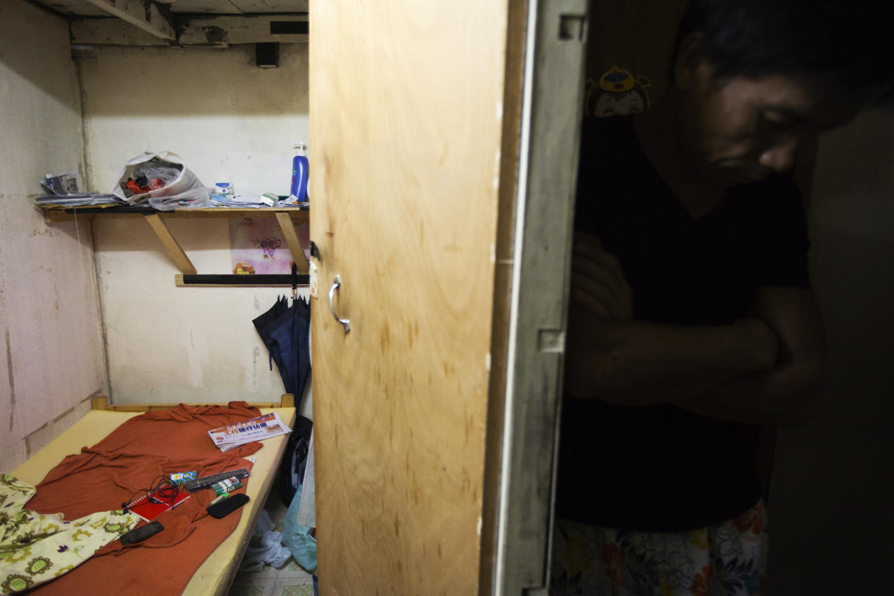A man stands next to a subdivided flat inside an industrial building in Hong Kong November 1, 2012. In October, Hong Kong leader Leung Chun-ying singled out the re-emergence of cage homes - wire mesh hutches stacked on top of each other - and cubicle apartments as issues that highlighted the gravity of poverty that existed alongside one of Asia's glittering financial centres. More than 1.1 million people, or 17 percent of Hong Kong's population, lived below the poverty line in 2011, earning less than HK$3,500 ($450) per month, according to the Hong Kong Council of Social Services. It defined poverty as earning less than half of the average monthly income. REUTERS/Tyrone Siu