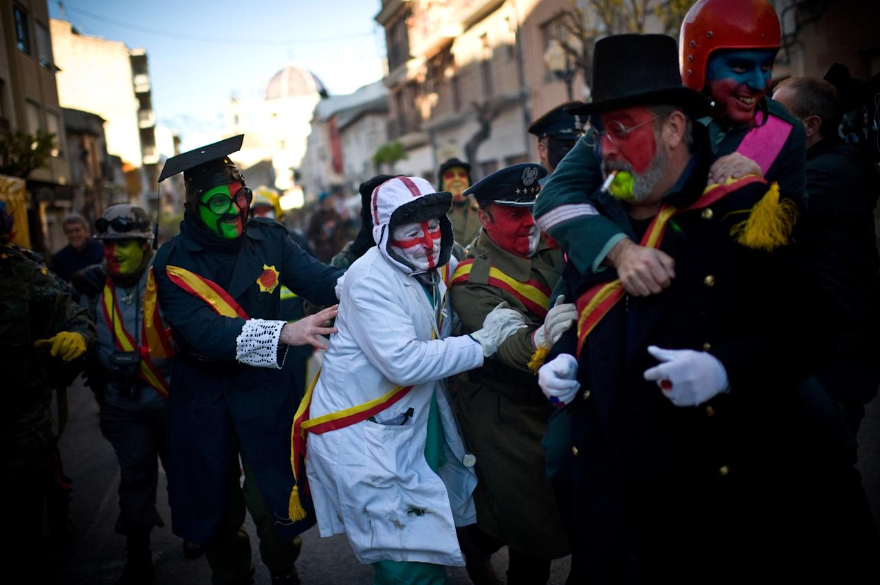 IBI, SPAIN - DECEMBER 28:  Revellers in fancy dress walk toward the battle of 'Enfarinats', a flour fight in celebration of the Els Enfarinats festival on December 28, 2012 in Ibi, Spain. Citizens of Ibi annually celebrate the festival with a battle using flour, eggs and firecrackers. The battle takes place between two groups, a group of married men called 'Els Enfarinats' which take the control of the village for one day pronouncing a whole of ridiculous laws and fining the citizens that infringe them and a group called 'La Oposicio' which try to restore order. At the end of the day the money collected from the fines is donated to charitable causes in the village. The festival has been celebrated since 1981 after the town of Ibi recovered the tradition but the origins remain unknown.Ê  (Photo by David Ramos/Getty Images)