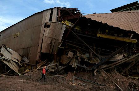FILE PHOTO: A member of a rescue team walks next to a collapsed tailings dam owned by Brazilian mining company Vale SA, in Brumadinho