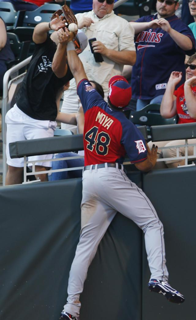 World's Steven Moya (48) fights with a fan trying to catch a foul ball hit by Team United States' Joey Gallo during the sixth inning of the All-Star Futures baseball game Sunday, July 13, 2014, in Minneapolis. (AP Photo/Paul Sancya)