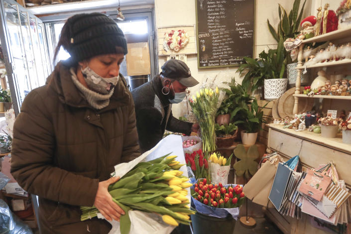 Staff members of a flower shop handle tulips in Budapest, Hungary, Wednesday April 7, 2021. Hungary's government lifted several lockdown restrictions on Wednesday, even as some doctors and medical experts urged caution after a record-breaking day of COVID-19 deaths, a move that came as Hungary reached 2.5 million first-dose vaccinations, a benchmark the government set for when a gradual reopening could move forward. (AP Photo/Laszlo Balogh)