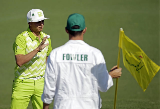 Rickie Fowler holds up his ball after putting on the first green during the first round of the Masters golf tournament Thursday, April 10, 2014, in Augusta, Ga. (AP Photo/Chris Carlson)