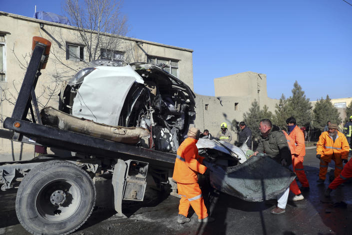 Afghan security personnel and municipality workers remove a damaged vehicle after a roadside bomb in Kabul, Afghanistan, Tuesday, Dec. 22, 2020. A roadside bomb tore through a vehicle in the Afghan capital of Kabul Tuesday, killing multiple people, police said. (AP Photo/Rahmat Gul)