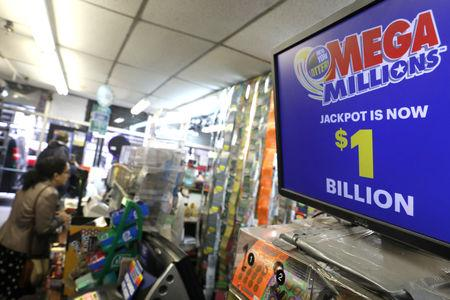A sign displays the jackpot for Mega Millions as customers buy lottery tickets in midtown Manhattan in New York, U.S., October 19, 2018.   REUTERS/Mike Sugar