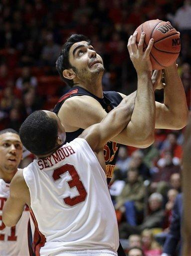 Utah guard Justin Seymour (3) fouls Southern California center Omar Oraby (55), of Egypt, in the first half during an NCAA basketball game Saturday, Jan. 12, 2013, in Salt Lake City. (AP Photo/Rick Bowmer)