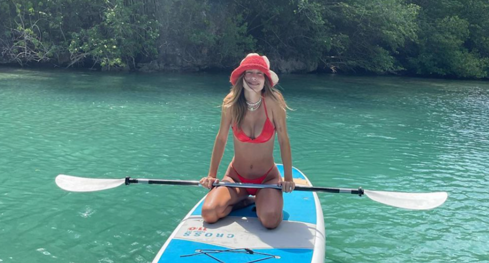 hailey bieber sitting on paddle board in water wearing red bikini and red bucket hat