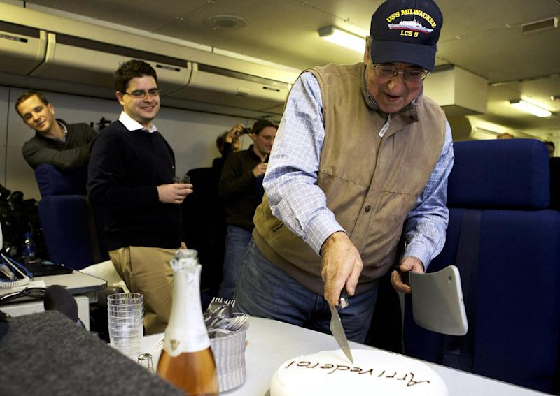 """The traveling staff on board the E-4B surprise U.S. Defense Secretary Leon Panetta with a cake that says """"arrivederci,"""" in a celebration in honor of the last leg of his final overseas trip as secretary, en route to Washington, Saturday, Jan. 19, 2013. The plastic meat axe at right was a joke gift from the staff, at the secretary's reference to budget sequestration being a meat axe. (AP Photo/Jacquelyn Martin)"""