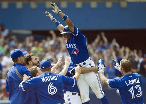Toronto Blue Jays' Rajai Davis, top, reacts with teammates after hitting the game-winning two-run home run against the Philadelphia Phillies during the tenth inning of interleague baseball game action in Toronto, Saturday, June 16, 2012. (AP Photo/The Canadian Press, Nathan Denette)