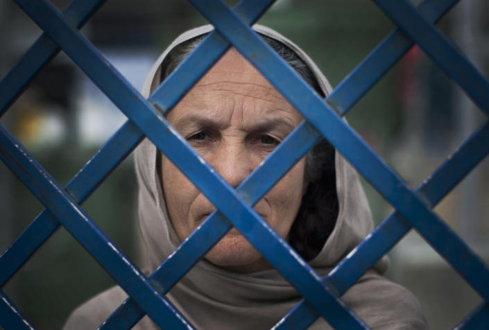 """Picture taken March 28, 2013 shows Afghan female prisoner Fauzia steering out of the prison bars at Badam Bagh, Afghanistan's central women's prison, in Kabul, Afghanistan. Fauzia is the oldest woman in jail and has served already seven years in jail. She will serve a 17 year sentence for killing her husband and her daughter-in-law. """"I was in one room. I came into the next room and they were there having sexual relations. I found a big knife and killed them both,"""" she said in a voice empty of emotion. (AP Photo/Anja Niedringhaus)"""